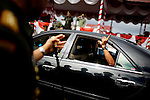 """Former Army General Soenarko holds up a """"number one"""" finger out the car window as he departs his post after a general handover event in Banda Aceh, Indonesia, on Nov. 20, 2009. ..Since the signing of Helsinki peace accord in 2005 that ended the longest conflict in Indonesia between the Free Aceh Movement and Indonesian government, the country has pulled out more then 20,000 troops from the province. The army base in Banda Aceh currently has about 15,000 soldiers."""