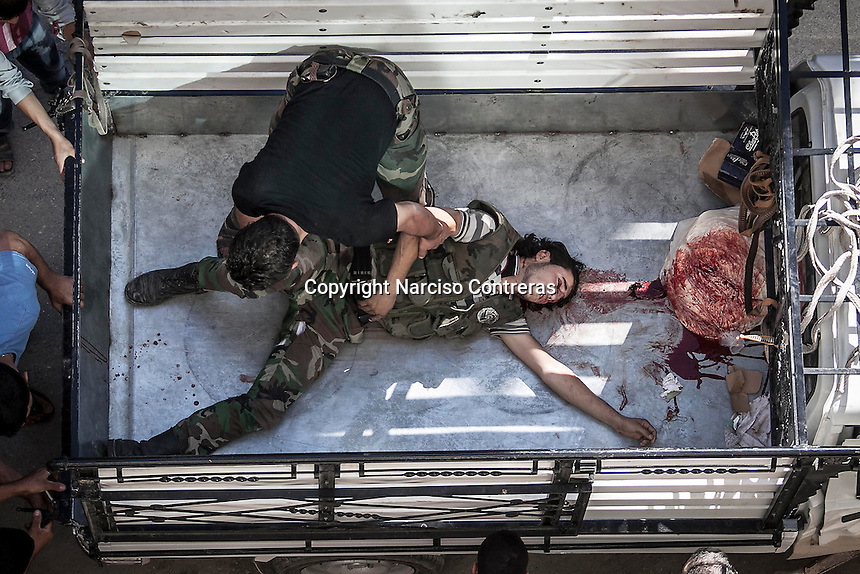 A rebel fighter pulls out the body of his wounded comrade shot at his head by sniper, from a truck to the hospital in Tarik Al Bab neighborhood, northeast of Aleppo City.