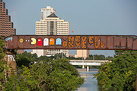 """Creative graffiti artist paint colorful and inspiring messages such as the """"Never Give Up"""" graffiti mural painting on the Austin Railroad Graffiti Bridge over Lady Bird Town Lake, Austin, Texas."""