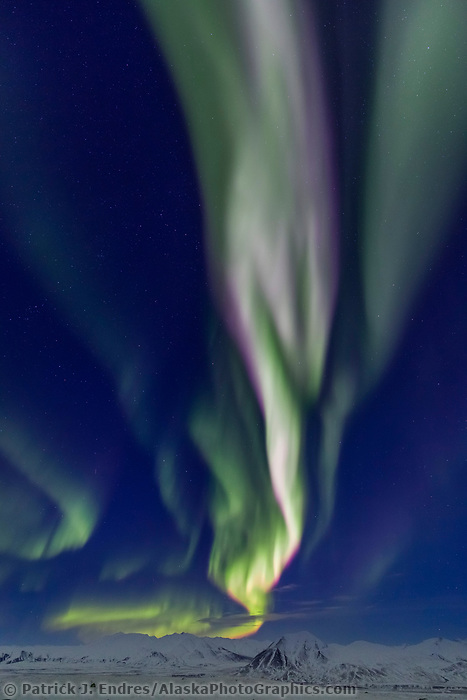 The northern lights arc high above the Philip Smith mountains in the Brooks Range, Arctic, Alaska.