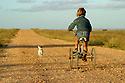 Young girl riding bike down a dusty road. Australia.