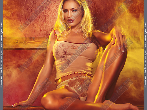 Glamour photo of a sexy young woman with long blond hair sitting in a steam room or sauna