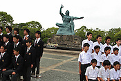 School children have their photographs taken in front of the 1955 sculpture by Seibo Kitamura in Nagasaki Peace Park, Tuesday May 24th 2005. The sculture marks the Nagasaki Atomic bombing blast on 9th August 1945.
