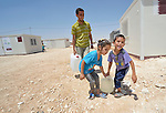 Elham Amwar gets help from his children Rema and Ayman as they carry water back to their family's shelter in the Zaatari refugee camp near Mafraq, Jordan. Established in 2012 as Syrian refugees poured across the border, the Zaatari camp held more than 80,000 refugees by 2015, and was rapidly evolving into a permanent settlement. ACT Alliance member agencies provide a variety of services to refugees living in the camp.