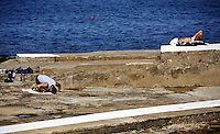 Beirut , Lebanon 20081026 - A man is praying and a man is sunbathing by the Corniche in Beirut. Photo/copyright: Torbjorn Gronning