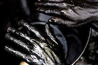 The hands of an oil can cleaner. Disused engine oil cans are collected and taken to Dharavi, once there they are throughly cleaned with petro chemicals and sold on.