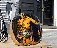 Mythic character painted on pumpkin holds the head of his victim in serious pumpkin art, Damariscotta Maine, 2010