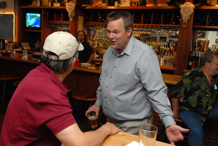 Senate candidate Jon Tester (D) talks with Dennis Alexander at a fundraiser at the Mint Bar and Cafe in Belgrade, Montana.