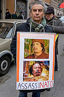 Rome, Italy. 16th January 2016<br /> Protester holding a sign with a picture of Colonel Muammar Gaddafi with the words: &quot;murdered&quot;, during Anti-war demonstration on the 25th anniversary of the bombings in Iraq and against military spending, organized by the union USB, and the social platform Eurostop.