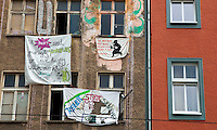 "Banners hang from a building in East Berlin where squatters are resisting eviction. One banner reads ""We don't need your ugly Yuppie Flats. We are happy with our Rats.""  Another banner says ""To Destroy what society has built is to create a new freedom"". ."