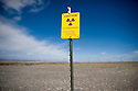 8/28/2008--Hanford, WA, USA..A radiation warning on the perimeter of the B-reactor at the Hanford Site, Washington, along the banks of the Columbia River. The reactor was the first large scale plutonium production reactor ever built and started production in December, 1944. The project was commissioned under the Manhattan Project, during World War II, to develop the first nuclear weapons. The B-Reactor was shut down in 1968 and on August 25th, 2008, was declared a National Historic Landmark and is now open to tourists...During the Cold War, the Hanford project was expanded to include nine nuclear reactors and five massive plutonium processing complexes, which produced plutonium for most of the 60,000 weapons in the U.S. nuclear arsenal. The weapons production reactors were decommissioned at the end of the Cold War, but the manufacturing process left behind 53 million U.S. gallons of high-level radioactive waste that remains at the site. Hanford is the most contaminated nuclear site in the United States and is the focus of the nation's largest environmental cleanup, providing thousands of jobs to residents in nearby towns such as Richland...©2008 Stuart Isett. All rights reserved.