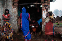 A family in front of their house at Laltenganj. This is one of the families still to be rehabilated. Laltenganj slum is one of the most affected areas by coal mine fire. A huge coal mine fire is engulfing the city of Jharia from all its sides. All scientific efforts have gone in vain to stop this raging fire. This fire is affecting lives of people living in and around Jharia. Jharkhand, India. Arindam Mukherjee