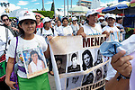 Lidia Diego (left) holds a photo of her daughter Nora Morales Diego as she walks with a group of Central Americans searching for family members who disappeared in Mexico. The demonstration took place in the center of Tapachula, Mexico, on December 16, 2013. The group, mostly mothers looking for their children, spent 17 days touring 14 Mexican states in search of their loved ones, most of whom had disappeared while following the migrant trail north.