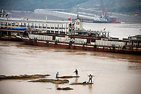 Men fish in the Yangtze River as barges pass by Chongqing, China. Increased river traffic and nearby manufacturing in the area has threatened the river's long-term ecology.