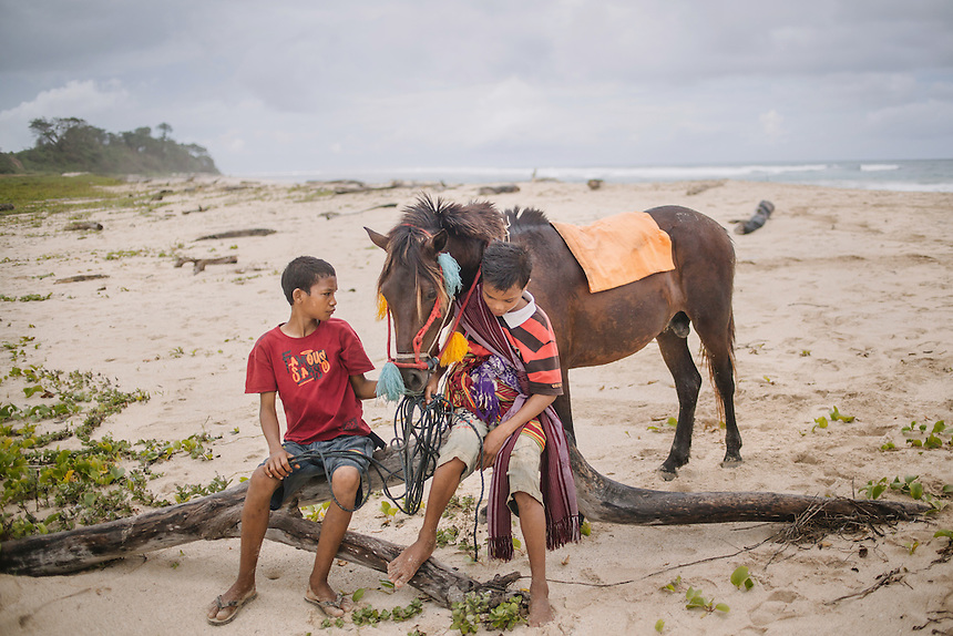 Sumbanese boys with a Pasola horse at the beach near the village of Wainyapu, Kodi. Pasola is an ancient tradition from the Indonesian island of Sumba. Categorized as both extreme traditional sport and ritual, Pasola is an annual mock horse warfare performed in response to the harvesting season. In the battelfield, the Pasola warriors use blunt spears as their weapon. However, fatal accident still do occurs.