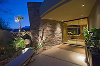 Night time view of stacked stone and glass entry way to modern residence