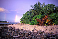 A rainbow rises vertically in the Pacific Ocean near the rocky shore of isolated Mili Atoll in the Marshall Islands.
