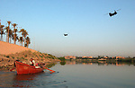 Two U.S. Army chinook helicopters pass an Iraqi fisherman as he works the Tigris River September 18, 2003 near downtown Baghdad, Iraq.