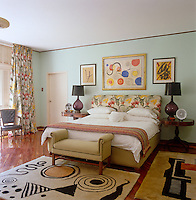 In this bedroom the wooden floor is covered with rugs with abstract designs inspired by modern artists whilst the curtains and bedhead are covered in a matching floral pattern