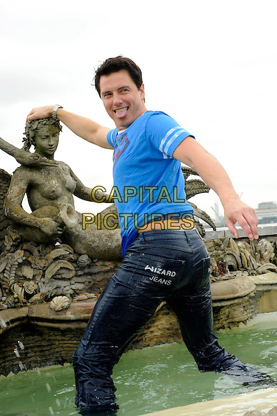 John Barrowman.Wizard Jeans Rear Of The Year Award 2012, Dorchester Hotel, London, England..June 27th, 2012.half length hand on hip thumb up looking over shoulder blue top t-shirt  mouth open tongue funny wet water fountain .CAP/CJ.©Chris Joseph/Capital Pictures.