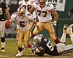 San Francisco 49ers quarterback Jeff Garcia (5) gets away from Oakland Raiders linebacker Travian Smith (56) on Sunday, November 3, 2002, in Oakland, California. The 49ers defeated the Raiders 23-20 in an overtime game.