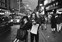 A couple eat chips on London's Oxford Street.