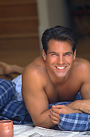 sexy man without a shirt smiling while enjoying time at home