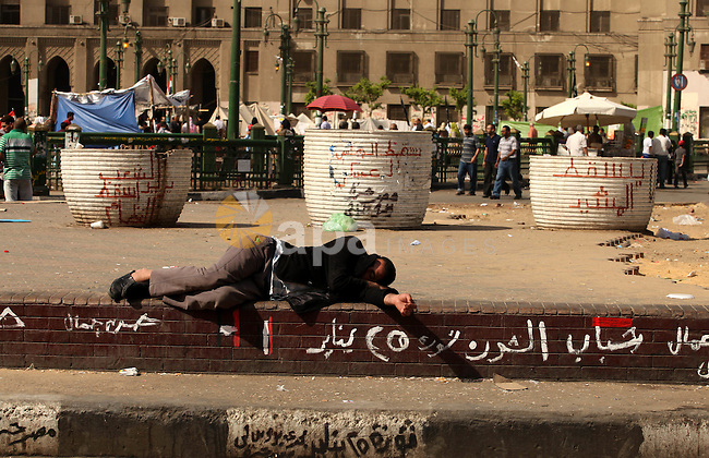 An Egyptian man sleeps on the ground in Cairo's landmark Tahrir Square on June 3, 2012 after a night of protests. Hundreds of demonstrators are occupying Tahrir Square after a court sentenced ousted president Hosni Mubarak and his interior minister Habib al-Adly to life in prison but acquitted six security chiefs in the deaths of protesters last year. Photo by Majdi Fathi