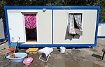 A small child bathes outside the shipping container that has been converted into its family's home home in Makis, a village outside of Belgrade, Serbia. This and dozens of other Roma families were evicted from Bellville, an urban squatter settlement, in 2012 to make way for construction of new apartments and office buildings. The shipping containers they now call home, which were provided at no cost by local authorities, are far from the city center.