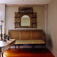 The dining room is furnished with a 19th century cane and bamboo settee and a 19th century English mirror