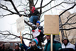 Fifteen-year-old John Aguirre, top, and his twelve-year-old sister, Marie, listen to protest speakers from a tree outside the  Wisconsin State Capitol over a bill that threatens to strip collective bargaining rights in Madison, Wisconsin, February 26, 2011. Crowds swelled Saturday as protests enter their 12th day.