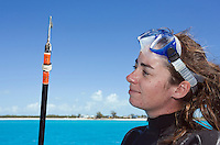 RR60276-D. Scientist Rachael Cashman from the Bimini Biological Field Station (aka the Sharklab) prepares to enter the ocean with with a polespear fitted with an orange acoustic tag. When she sees a Great Hammerhead Shark (Sphyrna mokarran) swimming below, Cashman will free-dive down to attach the tag to the shark, just below its dorsal fin. This tag will transmit an acoustic signal every 90 seconds which will be recorded by nearby receivers positioned around Bimini Island, allowing Sharklab researchers to monitor near shore local movement patterns of these elusive sharks about which we currently know very little. The scientists free-dive down to attach tags to free-swimming animals because this is much less harmful to the shark than catching the shark and bringing it up to the boat. Great hammerheads are at high risk of mortality when overstressed by invasive capture and handling. The tagging method used by the Sharklab avoids capture all together, critical to minimizing human impact on an endangered species whose populations are in decline. Bahamas, Atlantic Ocean.<br /> Photo Copyright &copy; Brandon Cole. All rights reserved worldwide.  www.brandoncole.com