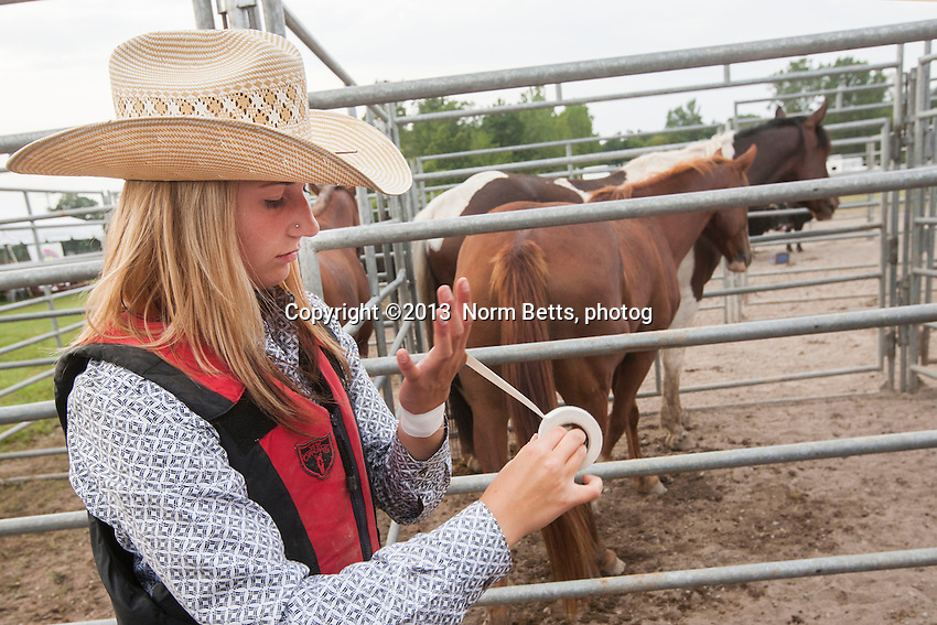 RIDES JUNIOR BULLS<br /> TAPES UP AN OLD INJURY BEFORE RODEO<br /> 15-year-old Dana Balaski, from Hendon, Saskatchewan,  competes in the RAM Rodeos in Ontario during her summer vacations.<br /> These images are from the RAM Rodeo Tour in Welland, Ontario, Canada<br /> Aug. 30, 2013<br /> Norm Betts, photographer<br /> 416 460 8743<br /> normbetts@canadianphotographer.com<br /> &copy;2013, normbetts, photographer