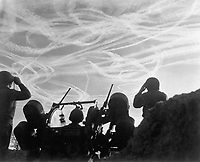 Alerted GIs of M-51 Anti-aircraft Battery are silhouetted against German sky streaked with vapor trails from allied and enemy planes engaged in Christmas Day dogfight.  Near Puffendorf, Germany.  December 25, 1944.  Pvt. M.S. Kelly. (Army)<br /> NARA FILE #:  111-SC-197661<br /> WAR &amp; CONFLICT BOOK #:  1084