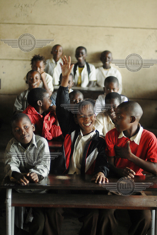 A student holds his hand up during a lesson at Forces Primary School.