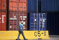 Man walking by a stack of shipping containers at the Port of Houston