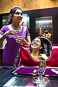 A store assistant shares a light moment with a young woman while she tries on gold jewelry at a Mehrasons Jewellers store in New Delhi, India. Photo: Sanjit Das/Panos Pictures