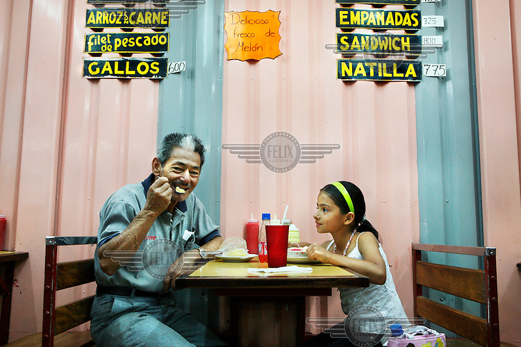 A father and daughter eating in a restaurant in the capital San Jose.