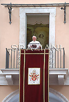 """In his first public appearance since having the cast removed from his broken right wrist, Pope Benedict XVI delivers his blessing during the Angelus prayer from his summer residence in Castel Gandolfo, on the outskirts of Rome, Sunday, Aug. 23, 2009. The pontiff jokingly said that his hand was """"freed"""" but still a bit sluggish. Benedict clearly favored his left hand while blessing the faithful gathered in the courtyard of the papal summer residence, but he was able to bless the crowd with his right hand. The wrist remained covered with a white bandage."""