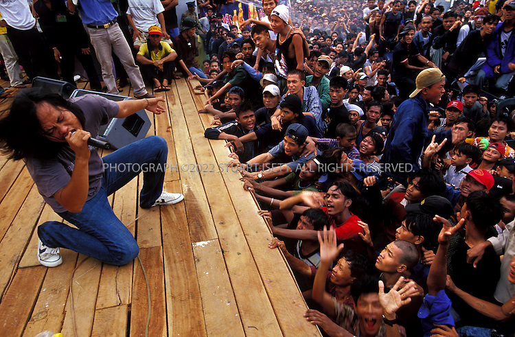4/13/2002--Rangoon, Burma..Lay Phyu leans back and belts out a tune during an Iron Cross concert...The annual outdoor free concerts are held every April duirng Burma's traditional New Year celebrations. Normally gatherings of young men woiuld be broken up by Burma's ruling junta but the concerts are the one time of year such large gatherings are allowed. Local authorities are nervous that such concerts may turn political or violent and watch the shows carefull for signs of unrest...All photographs ©2003 Stuart Isett.All rights reserved.