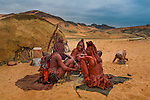 A group of Himba tribeswomen gather around a fire, Namibia.