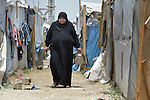 A woman walks in a settlement of Syrian refugees in Minyara, a village in the Akkar district of northern Lebanon. Lebanon hosts some 1.5 million refugees from Syria, yet allows no large camps to be established. So refugees have moved into poor neighborhoods or established small informal settlements in border areas. International Orthodox Christian Charities, a member of the ACT Alliance, provides a variety of support for families in this settlement, including some meals prepared in a community kitchen.