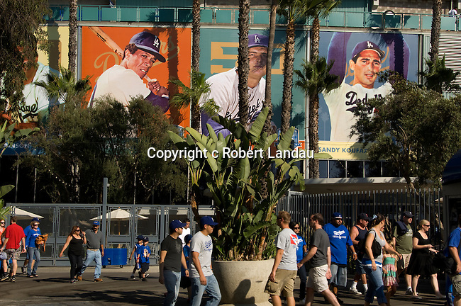 Ddoger fans arriving at dodger Stadium beneath portraits of great players from the past.