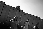 Palestinian boys play football on a school pitch in front of the controversial Israel separation barrier in the West Bank village of Anata, on the outskirts of Jerusalem on June 8, 2010.&copy; ALESSIO ROMENZI