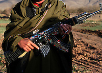 The convoy has been guarded all might by Warlord Matiuallah's men. This one policemen has a colourfully decorated AK47.