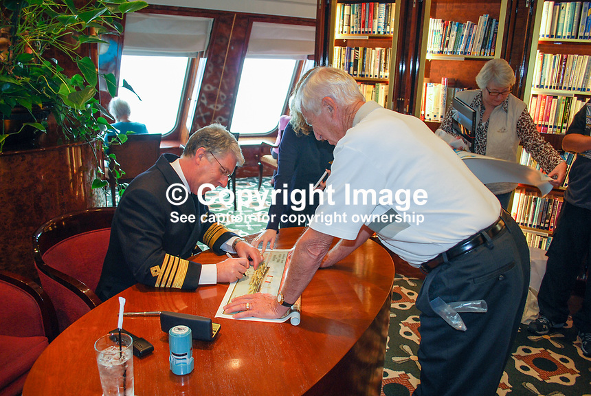 Captain Kevin Oprey, skipper, Queen Mary 2, signing memorabilia for passengers in the ship's library. 2011285614..Copyright Image from Victor Patterson, 54 Dorchester Park, Belfast, United Kingdom, UK...For my Terms and Conditions of Use go to http://www.victorpatterson.com/Victor_Patterson/Terms_%26_Conditions.html