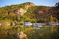 Boats on Dalyan Çayı River with Lycian Rock Tombs in the cliffs . Mediterranean coast Turkey