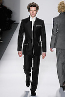 Model walks runway in a men's black loro piana cashmere/wool upturened peak lapel suit w/ivory top-stitching, ivory italian silk dupioni dress shirt+bow tie, from the Zang Toi Fall 2012 &quot;Glamour At Gstaad&quot; collection, during Mercedes-Benz Fashion Week New York Fall 2012 at Lincoln Center.
