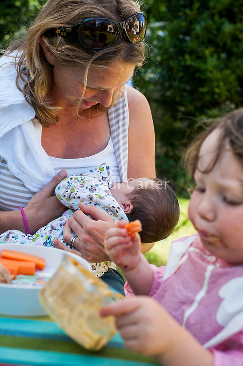 A young mother breastfeeds her new baby whilst her toddler feeds herself carrot and houmous at a table in the garden on a summer's day.<br /> <br /> 26/08/12<br /> Hampshire, England, UK