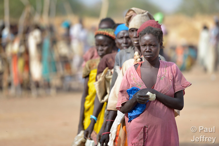 Women line up to receive food from the ACT Alliance in Rumading, a village in South Sudan's Lol State where more than 5,000 people, displaced by drought and conflict, remain in limbo. In early 2017, they set out walking for Sudan, seeking better conditions, but were stopped from crossing the border. They remain camped out under the trees at Rumading, eating wild leaves as the rainy season approaches. <br /> <br /> In early April, Norwegian Church Aid, a member of the ACT Alliance, began drilling a well in the informal settlement and distributed sorghum, beans and cooking oil to the most vulnerable families, including these women. The ACT Alliance is carrying out the emergency assistance in coordination with government officials and the local Catholic parish.